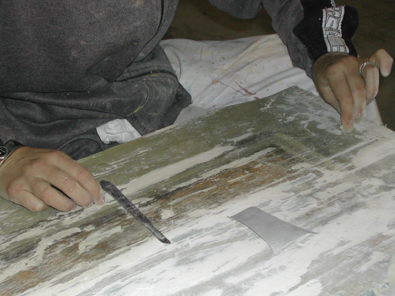 Rasatura dello stucco con carte abrasive e bisturi